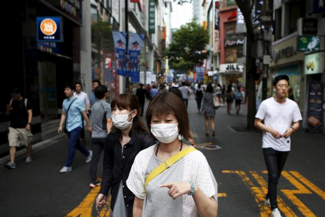 Women wearing masks to prevent contracting Middle East Respiratory Syndrome (MERS) walk at Myeongdong shopping district in central Seoul, South Korea, July 9, 2015. REUTERS/KIM HONG-JI