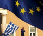 A protester waves a Greek flag at the entrance of the parliament building during a rally calling on the government to clinch a deal with its international creditors and secure Greece's future in the Eurozone, in Athens, Greece, in this June 22, 2015 file photo. REUTERS/Yannis Behrakis/Files