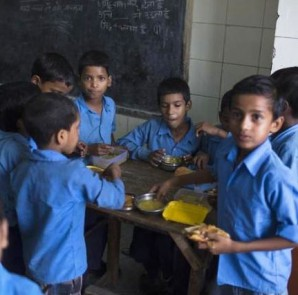FILE PHOTO: School boys eat their free mid-day meal, distributed by a government-run primary school, inside their classroom in New Delhi July 19, 2013. REUTERS/AHMAD MASOOD/FILES