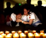 A family member cries as she and other relatives pray during a candlelight vigil for passengers onboard the missing Malaysia Airlines Flight MH370 in the early morning, at Lido Hotel, in Beijing April 8, 2014. REUTERS/JASON LEE