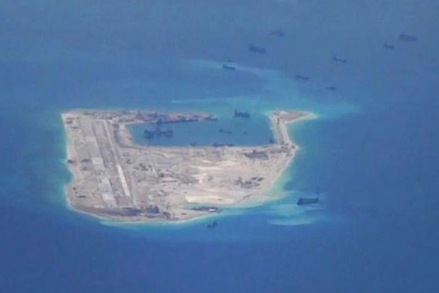 Chinese dredging vessels are purportedly seen in the waters around Fiery Cross Reef in the disputed Spratly Islands in the South China Sea in this still image from video taken by a P-8A Poseidon surveillance aircraft provided by the United States Navy May 21, 2015. REUTERS/U.S. NAVY/HANDOUT VIA REUTERS