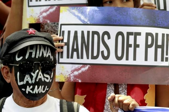 """An activist wears a black mask with a message reading """"China Get Out!"""" as they protest against Beijing's activities in the South China Sea outside the Chinese consulate in Makati city, metro Manila July 7, 2015. REUTERS/Romeo Ranoco"""