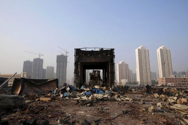 A damaged building is seen among debris at the site of Wednesday night's explosions in Binhai new district of Tianjin, China, August 15, 2015. REUTERS/CHINA DAILY CHINA OUT.