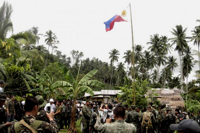 FILE PHOTO: Filipino soldiers raise a Philippine flag at a seized camp of Abu Sayyaf militants on Jolo island in southern Philippines on Sept 21, 2009. (REUTERS)