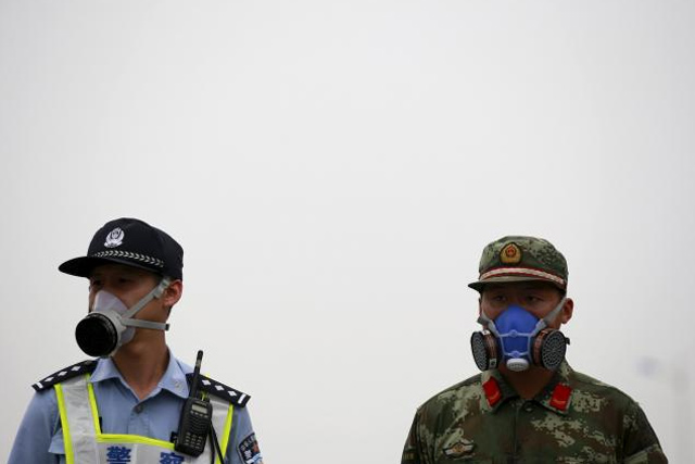 A paramilitary policeman and a policeman, both wearing masks, stand guard at a location within a 3-km (2-mile) exclusion zone from last week's explosion site in Binhai new district in Tianjin, China, August 18, 2015. REUTERS/KIM KYUNG-HOON