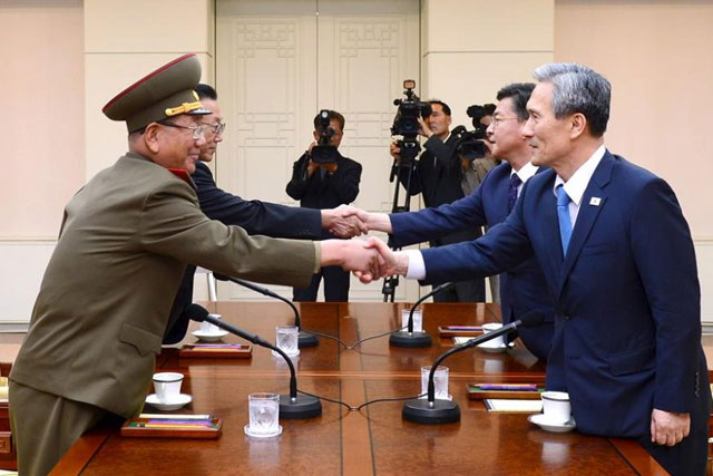 South Korean National Security Adviser Kim Kwan-jin (R), South Korean Unification Minister Hong Yong-pyo (2nd R), Secretary of the Central Committee of the Workers' Party of Korea Kim Yang Gon (2nd L), and the top military aide to the North's leader Kim Jong Un Hwang Pyong-so (L), shake hands, August 22, 2015. REUTERS/the Unification Ministry/Yonhap