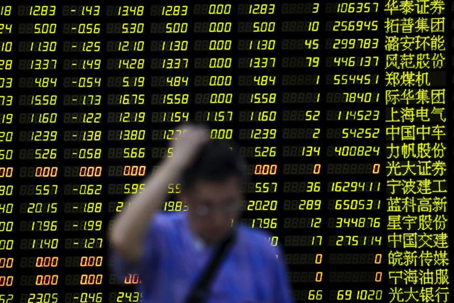 An investor stands in front of an electronic board showing stock information at a brokerage house in Shanghai, China, August 24, 2015. REUTERS/Aly Song