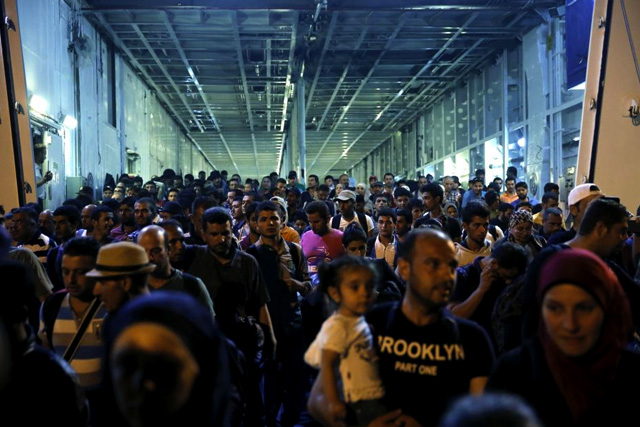 """Refugees and migrants disembark from the passenger ship """"Tera Jet"""", following their trip from the island of Lesbos to the port of Piraeus, near Athens, Greece September 1, 2015. REUTERS/Alkis Konstantinidis"""