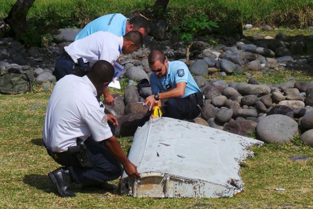 File picture shows French gendarmes and police inspecting a large piece of plane debris which was found on the beach in Saint-Andre, on the French Indian Ocean island of La Reunion, July 29, 2015 REUTERS/ZINFOS974/PRISCA BIGOT/FILES