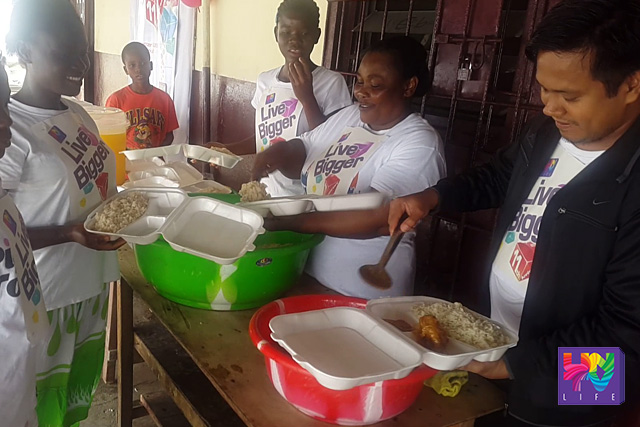 UNTV Correspondent and MCGI African members seen serving food for the locals at a feeding program as part of UNTV's 11th Anniversary  celebration. (UNTV News)