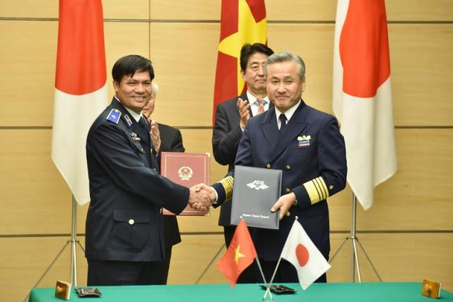 Major General Nguyen Quang Dam (L), Commander of the Vietnam Marine Police, and Admiral Yuji Sato (R), Commandant of the Japan Coast Guard, exchange documents during a signing ceremony while Vietnamese Communist Party General Secretary Nguyen Phu Trong (rear L) and Japan's... REUTERS/KAZUHIRO NOGI/POOL