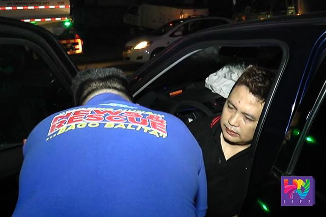 Ang naaksidenteng si Rey John Delos Reyes habang nilalapatan ng UNTV News and Rescue ng first aid matapos bumangga sa concrete barrier ang kotse nito. (UNTV News)