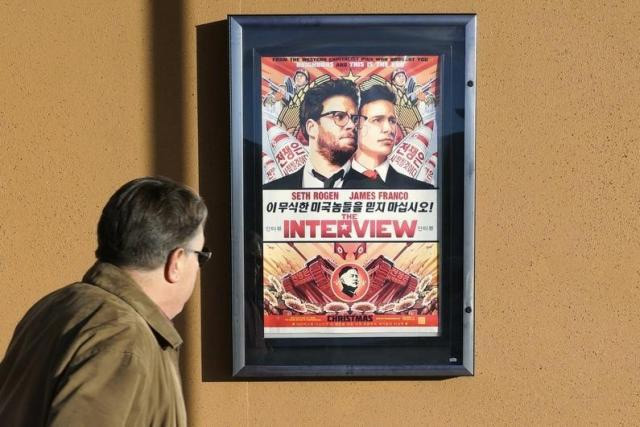 A man walks by the poster for the film ''The Interview'' outside the Alamo Drafthouse theater in Littleton, Colorado December 23, 2014. REUTERS/RICK WILKING