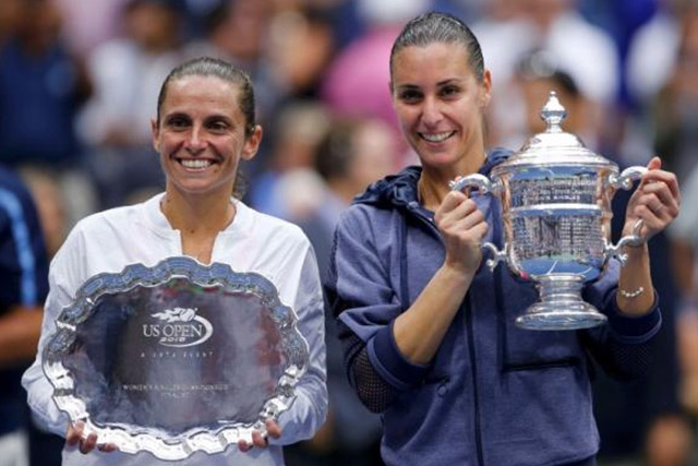 Flavia Pennetta of Italy (R) holds her U.S. Open Trophy next to compatriot Roberta Vinci during the award presentation ceremony following their women's singles final match at the U.S. Open Championships tennis tournament in New York, September 12, 2015. REUTERS/EDUARDO MUNOZ