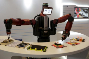 A Baxter robot of Rethink Robotics picks up a business card as it performs during a display at the World Economic Forum (WEF), in China's port city Dalian, Liaoning province, China, September 9, 2015. REUTERS/JASON LEE