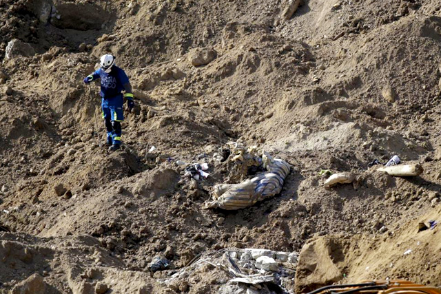 A rescue team member searches for bodies at a mudslide-affected area, in Santa Catarina Pinula, on the outskirts of Guatemala City, October 7, 2015. REUTERS/Josue Decavele