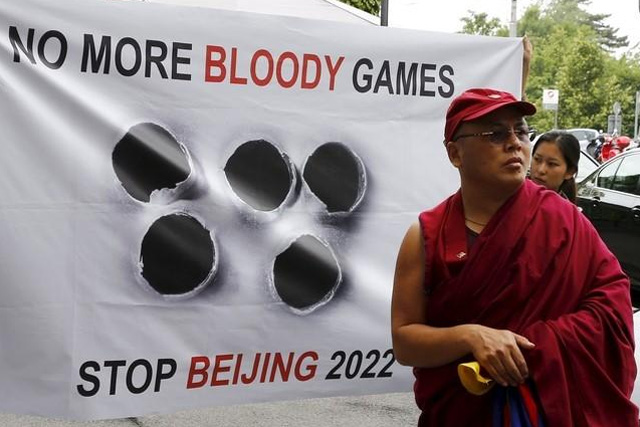 Tibetan monk Golog Jigme stands in front of a banner outside the Beijing 2022 Winter Olympic Candidate City presentation at the Palace hotel in Lausanne, Switzerland in this June 10, 2015 file photo. REUTERS/Ruben Sprich/Files