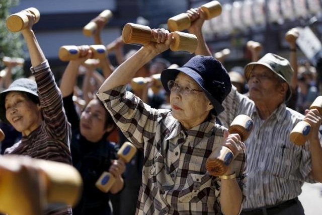 Elderly and middle-age people exercise with wooden dumbbells during a health promotion event to mark Japan's ''Respect for the Aged Day'' at a temple in Tokyo's Sugamo district, an area popular among the Japanese elderly, September 21, 2015. REUTERS/ISSEI KATO