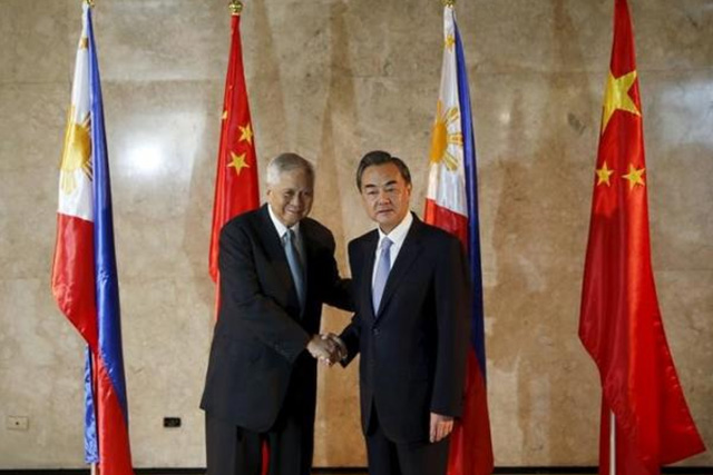 Philippine Foreign Secretary Albert del Rosario (L) shakes hands with visiting Chinese Foreign Minister Wang Yi in front of the Philippine and Chinese flags at the Department of Foreign Affairs in Manila November 10, 2015. REUTERS/ERIK DE CASTRO