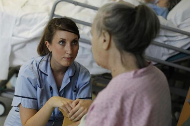 Health Care Assistant Sophie Dorrington talks to a patient in the stroke ward at Hinchingbrooke Hospital in Huntingdon, eastern England November 3, 2011. REUTERS/SUZANNE PLUNKETT