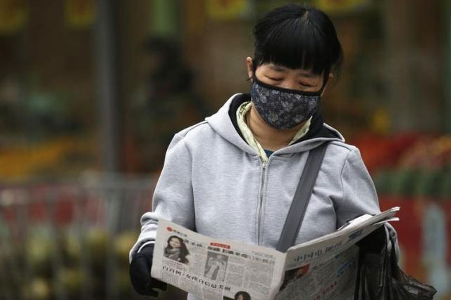 A woman wearing a facial mask reads a newspaper along a street on a hazy day in Beijing March 27, 2014. REUTERS/KIM KYUNG-HOON/FILES