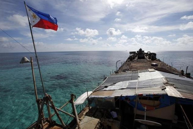 A Philippine national flag flutters in the wind aboard the BRP Sierra Madre, run aground on the disputed Second Thomas Shoal, part of the Spratly Islands, in the South China Sea March 29, 2014. REUTERS/ERIK DE CASTRO