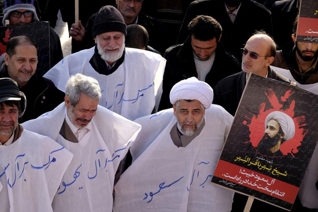 An Iranian cleric holds a picture of prominent Shi'ite cleric Sheikh Nimr al-Nimr during a demonstration against the execution of al-Nimr in Saudi Arabia, at Imam Hussein square in Tehran January 4, 2016. REUTERS/Raheb Homavandi/TIMA