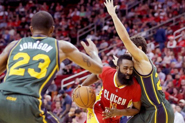 Jan 7, 2016; Houston, TX, USA; Houston Rockets guard James Harden (13) drives as he splits the defense of Utah Jazz forward Chris Johnson (23) and guard Raul Neto (25) in the second half at Toyota Center. Rockets won 103 to 94. USA TODAY Sports -