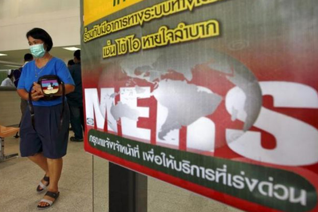 A woman wearing a mask walks past an information banner on Middle East Respiratory Syndrome (MERS) at the entrance of Bamrasnaradura Infectious Diseases Institute in Nonthaburi province, on the outskirts of Bangkok, Thailand, June 19, 2015. REUTERS/CHAIWAT SUBPRASOM