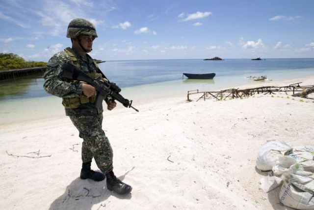 A Filipino soldier patrols at the shore of Pagasa island (Thitu Island) in the Spratly group of islands in the South China Sea, west of Palawan, Philippines, May 11, 2015. REUTERS/RITCHIE B. TONGO/POOL