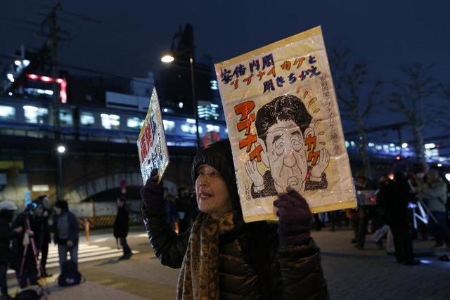 A protester holds banners depicting Japan's Prime Minister Shinzo Abe as she shouts during an anti-nuclear rally in front of the headquarters of Tokyo Electric Power Co (TEPCO), the operator of the tsunami-crippled Fukushima Daiichi nuclear plant, a day before the five-year anniversary of the disaster, in Tokyo, Japan, March 10, 2016. REUTERS/Yuya Shino