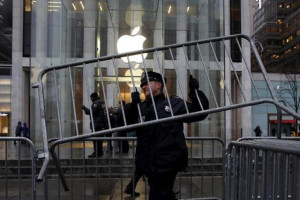 A NYPD officer carries a barrier outside the Apple Store in New York February 23, 2016. REUTERS/SHANNON STAPLETON