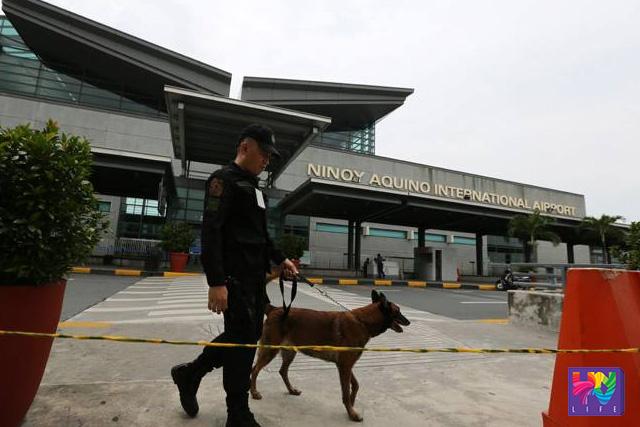 FILE PHOTO: Isang pulis na may kasamang bomb-sniffing dog sa entrance ng Ninoy Aquino International Airport noong September 01, 2014. (Photoville International)
