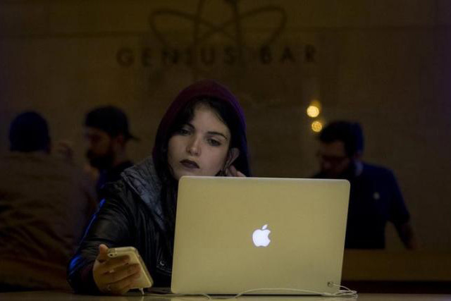 A customer uses an iPhone and a Macbook computer at the Genius Bar in the Apple Store at Grand Central Station in New York April 20, 2015. REUTERS/BRENDAN MCDERMID