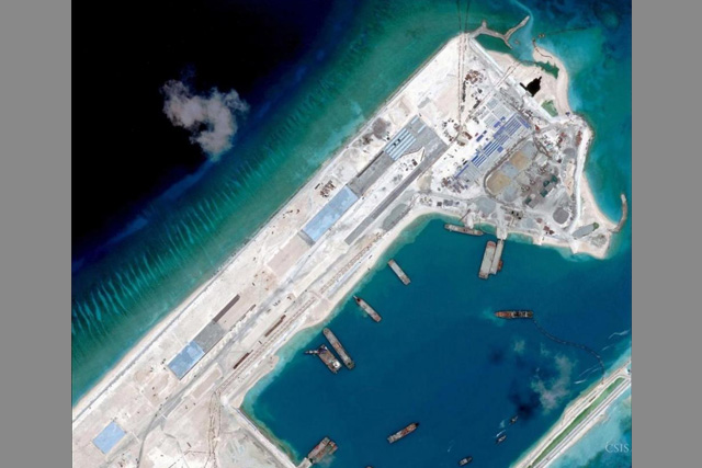 FILE PHOTO: Airstrip construction on the Fiery Cross Reef in the South China Sea is pictured in this April 2, 2015 handout satellite image obtained by Reuters on April 16, 2015. REUTERS/CSIS Asia Maritime Transparency Initiative/DigitalGlobe/Handout via Reuters