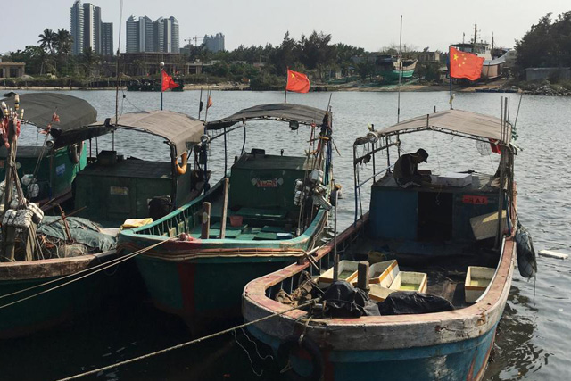 Saturday, April 30, 2016 Fishing boats with Chinese national flags are seen at a harbour in Tanmen, Hainan province, April 5, 2016. REUTERS/Megha Rajagopalan