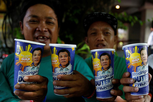 """Tuesday, May 03, 2016 Mall parking attendants and supporters of presidential candidate Rodrigo Duterte for the May 9 election, pose with """"Big Gulp"""" soda cups they bought from convenience store 7-Eleven, in Paranaque, Metro Manila, Philippines April 25, 2016. REUTERS/Erik De Castro"""