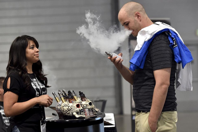 Jerred Marsh (R) samples flavored vape juice from Nancy Reyes at the Vape Summit 3 in Las Vegas, Nevada May 2, 2015. REUTERS/David Becker/File Photo