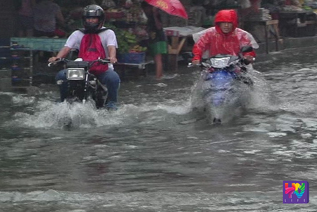 Two motorists cross the flooded road.