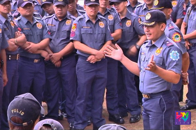 FILE PHOTO: PNP personnel gather round before a police officer. (UNTV News)
