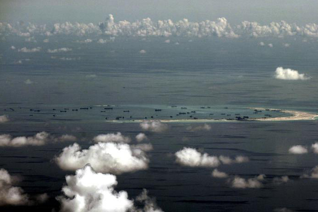 Tuesday, June 07, 2016 An aerial photo taken though a glass window of a Philippine military plane shows the alleged on-going land reclamation by China on mischief reef in the Spratly Islands in the South China Sea, west of Palawan, Philippines, May 11, 2015. REUTERS/Ritchie B. Tongo/Pool
