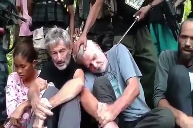Abu Sayyaf member threatens to behead a foreign hostage in this file photo.
