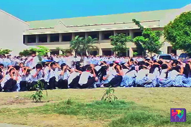 FILE PHOTO: Students perform the Duck. Cover. Hold' in an earthquake drill.