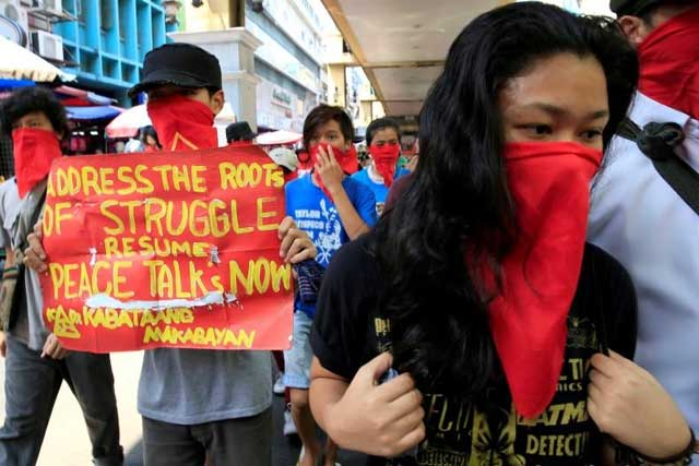 Tuesday, June 21, 2016 Supporters of the communist National Democratic Front (NDF) of the Philippines cover their faces and display a placard as they call for the resumption of peace talks between the government and the Maoist-led rebels, during a protest along a main road in metro Manila, Philippines June 16, 2016. REUTERS/Romeo Ranoco