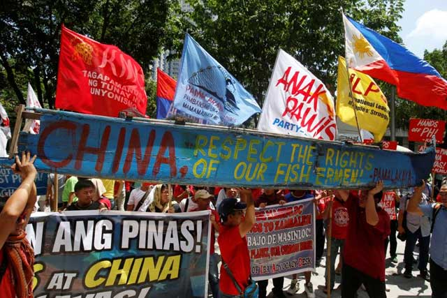 Tuesday, July 12, 2016 Demonstrators display a part of a fishing boat with anti-China protest signs during a rally by different activist groups over the South China Sea disputes, outside the Chinese Consulate in Makati City, Metro Manila, Philippines July 12, 2016. REUTERS/Erik De Castrby