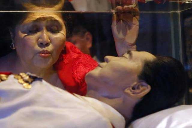 Former first lady Imelda Marcos kisses the glass coffin of her husband, late president Ferdinand Marcos, who remains unburied since his death in 1989, during her 85th birthday celebration in Ferdinand Marcos' hometown of Batac, Ilocos Norte province, in northern Philippines... REUTERS/ERIK DE CASTRO