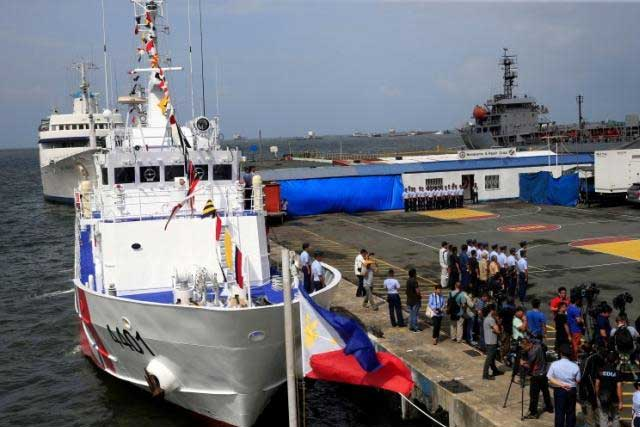 A Philippine flag flutters in front of the BRB Tubbataha, a coast guard ship, one of 10 multi-role vessel the Philippines is acquiring from Japan under a 8.8 billion pesos (US$ 190million) agreement, as it arrives in south harbor, metro Manila, Philippines August 18, 2016. REUTERS/Romeo Ranoco