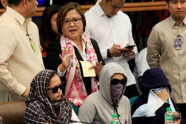 Senator Leila De Lima, chairperson of the Committee on Justice and Human Rights, gestures as she stands near relatives of slain people during a Senate hearing investigating drug-related killings at the Senate headquarters in Pasay city, metro Manila, Philippines August 22, 2016. REUTERS/Romeo Ranoco