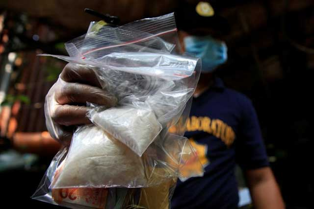 A member of the Philippine National Police (PNP) investigation unit shows confiscated methamphetamine, known locally as Shabu, along with Philippines pesos seized from suspected drug pushers during an operation by the police in Quiapo city, metro Manila, Philippines July 3,... REUTERS/Romeo Ranoco