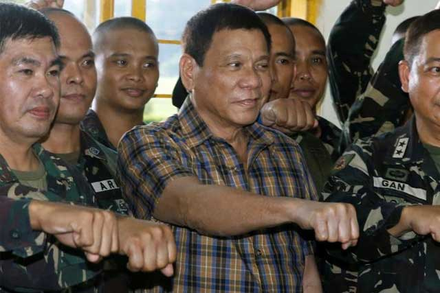 Philippine President Rodrigo Duterte makes a 'fist bump', his May presidential elections campaign gesture, with soldiers during a visit at Capinpin military camp in Tanay, Rizal in the Philippines August 24, 2016. REUTERS/Erik De Castro